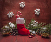 Christmas stocking Pine cones and branches snowflake and candy Christmas decorations  red wooden rustic background  close up Royalty Free Stock Images