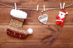 Christmas stocking, santa and heart hanging on brown wooden background, decorative xmas toys on wood table, buying presents shoppi royalty free stock photography