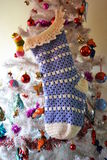 Christmas Stocking on Tree. Blue crocheted Christmas stocking hanging on a tree Stock Photos