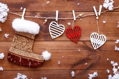 Christmas stocking, white red hearts hanging on brown wooden background, xmas valentines day card, copy space, top view stock photo