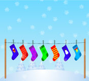 Christmas Stockings 3. Vector Christmas Stockings hanging on a rope, on winter landscape background Royalty Free Stock Photography