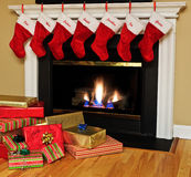 Christmas stockings by the fireplace. Red Christmas stockings hang from the mantle over a blazing fireplace on Christmas Eve, with a pile of Christmas presents Royalty Free Stock Photography