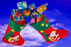 Christmas stockings and gifts in the sky. Royalty Free Stock Photography