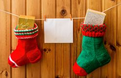 Christmas stockings and greeting card on wooden wall Royalty Free Stock Photos