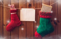 Christmas stockings and greeting card on wooden wall. Royalty Free Stock Photo