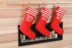 Christmas stockings hanging on wooden wall near decorative fireplace. Festive interior stock images