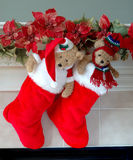 Christmas Stockings on the Mantle. Red and white fur christmas stockings, each with a stuffed bear inside, hang on the mantle above the fireplace on Christmas Stock Photo