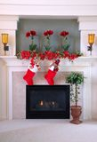 Christmas Stockings on the Mantle. Red and white fur christmas stockings hang on the mantle above the fireplace Royalty Free Stock Photos