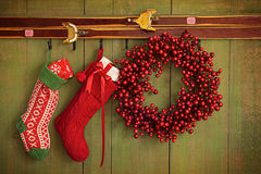 Christmas stockings and wreath hanging on wall stock photography