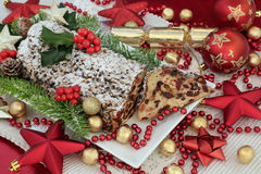 Christmas Stollen Cake. Traditional christmas chocolate stollen cake on a plate with slice, red and gold bauble decorations, foil wrapped chocolates, holy and Royalty Free Stock Image