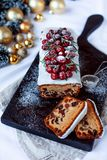 Christmas stollen with several ingredients on black wooden board decorated with berries and sugar powder. Flat lay stock images