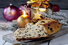 Christmas stollen on wooden board with candles christmas bulbs cinnamon stars cinnamon sticks pine twig present Stock Photo