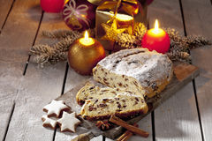 Christmas stollen on wooden board with candles christmas bulbs cinnamon stars cinnamon sticks pine twig present Stock Photos