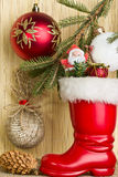 Christmas story - a branch of spruce, Santa's boots, balls and p Royalty Free Stock Photos