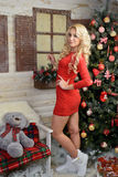 Christmas story or dream in Christmas. Merry girl in red dress standing next to a Christmas elkoy.ryadom on the bench is a teddy bear. Volgograd region, Russia Stock Image