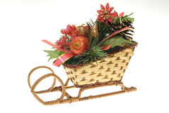 Christmas straw sleigh. Stylized wicker christmas straw sleigh with strobiles, gold, red present and balls, fir-tree's leafs isolated on white stock photo