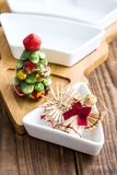 Christmas straw toys and bowl with salt shaker on wood Royalty Free Stock Images