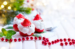 Christmas strawberry Santa. Funny dessert stuffed with whipped cream Stock Photo