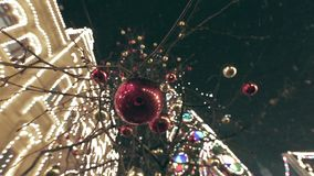 Christmas Street Decoration. Building, trees in garlands. Red and yellow decorative balls hanging on the trees against background with illuminated building stock video footage