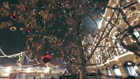 Christmas Street Decoration. Building, trees in garlands. Red and yellow decorative balls hanging on the trees against background with illuminated building stock video