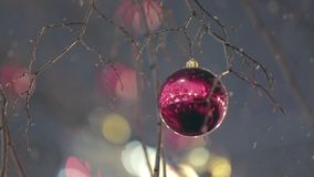 Christmas Street Decoration. Building, trees in garlands. Red and yellow decorative balls hanging on the trees against background with illuminated building stock footage