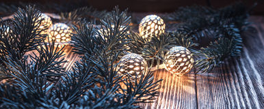 Christmas string lights and fir branches on wooden background. vintage garland and bokeh. Royalty Free Stock Photo