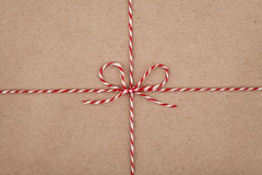 Christmas string or twine tied in a bow on kraft paper texture Stock Image