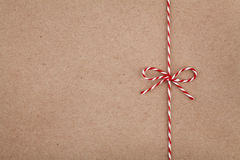 Christmas string or twine tied in bow on kraft paper texture Royalty Free Stock Photo