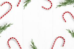 Christmas styled stock photo. White wooden background with candy cane decorations, evergreen juniperus branches and. Empty space, top view. Festive composition stock photo