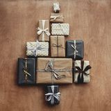 Christmas stylish gift boxes in tree shape on rustic wooden back stock image