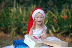 Christmas in summer. A full body of a beautiful blond blue eyed caucasian white girl child with happy and  excited expression in the pretty face wearing a red Stock Photo