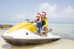 Christmas Summer Fun. Mother and daughter pose together on a jetski in the Cayman Islands at Christmas time Royalty Free Stock Photography