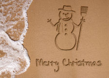 Christmas in Summer. Sunny Christmas illustration: A snowman and Merry Christmas written in the sand on the beach next to the ocean Stock Images