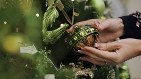 Close up shot of a woman shopping for christmas toys alone. Close-up of female hand picks a Christmas ball and examines. Christmas supermarket. Woman chooses stock footage