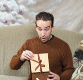 Christmas Surprise. A young man looks surprised at what he sees for his Christmas present Stock Photos