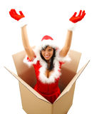 Christmas surprise. Attractive female Santa coming out from a big box with hands up Stock Photo