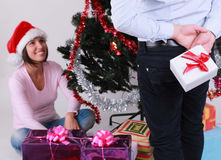 Christmas surprise. A men hiding gift behind his back in front of a happy young women near the Christmas Tree Royalty Free Stock Photo