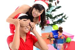 Christmas surprise. Image of a couple on Christmas, girl covering guy�s eyes to surprise him Stock Images
