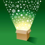 Christmas surprise. A vector illustration of an open box, light and snowflakes coming out of it Stock Images