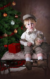 Christmas Surprise. Young Toddler boy in old-fashioned knickers outfit, holding tabby kitten stock photo