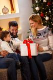 Christmas surprise in box. Parents giving Christmas surprise in box to their son stock photography