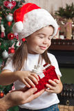 Christmas surprise from father for little girl in Santa hat Royalty Free Stock Photos