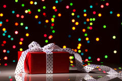 Christmas surprise. Gift box with silk bow on colorful bokeh background Royalty Free Stock Photos
