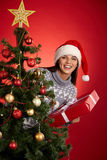 Christmas surprise. Joyful female in Santa cap looking at camera out of decorated xmas tree stock photo