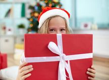 Christmas surprise. Portrait of happy girl peeking out of big red giftbox on Christmas evening Royalty Free Stock Image