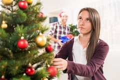 Christmas Surprise. Young beautiful girl decorates a Christmas tree while her boyfriend holds a Christmas gift and he wants to surprise her Stock Photos