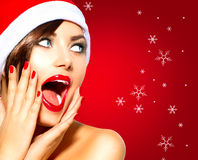 Christmas Surprised Winter Woman. Beauty Model Girl in Santa Hat Royalty Free Stock Images
