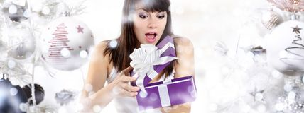 Christmas surprised woman opening gift present box on christmas. Background with balls and blurred lights royalty free stock photo