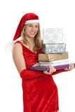 Christmas surprises. Young girl in santa outfit with a pile of presents Royalty Free Stock Image