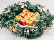 Christmas sushi. New Year sushi. Sushi and Christmas wreath. The word SUSHI from wooden beeches stock image